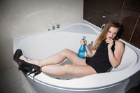 Young nice blonde posing in a bath
