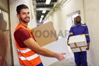 Lächelnder Arbeiter mit Warnweste trägt Pakete