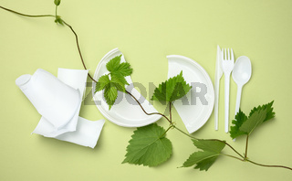 broken white plastic plate, fork, knife and branch with green leaves on a green background. The concept of avoiding plastic, preserving the environment