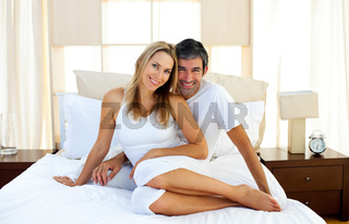 Affectionate lovers embracing on bed
