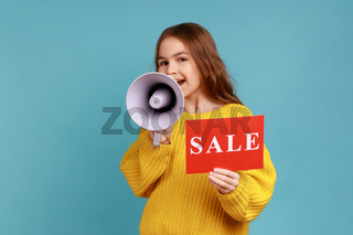 Portrait of cute little girl announcing in megaphone discounts in children department in the store.