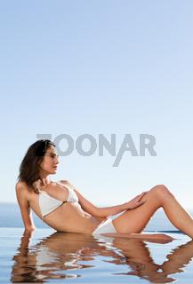 Woman enjoying the sun on pool edge