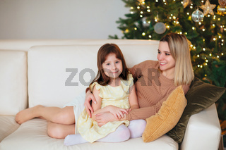 Happy playful little girl daughter playing with positive mother, jumping on sofa, spending time together during Christmas holidays at home