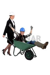 businesswoman carrying a craftswoman in a wheelbarrow