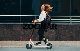 Young woman with smile ride electric scooter at the street