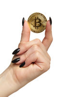 Female hand with black nails manicure and golden bitcoin in fingers. Isolated on white background.