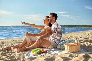 happy couple having picnic on summer beach
