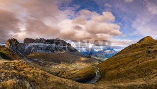 Autumn Dolomites mountain scene from hiking path betwen Pordoi Pass and Fedaia Lake, Italy. Snowy Marmolada massif and Glacier in far right.