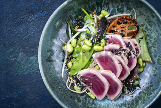 Modern style traditional Japanese gourmet seared tuna fish steak tataki with soba noodles and stir-fried vegetables served as top view on a Nordic design bowl with copy space left