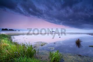 misty sunrise over wild lake