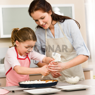 Decorating cake mother and daughter