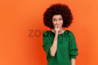 Funny woman with Afro hairstyle wearing green casual style sweater picking her nose, demonstrating bad manners, childish behavior.