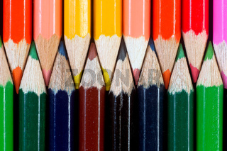 Colorful pencils on dark background lined up