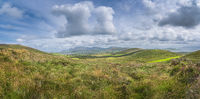 Large panorama with valley, green fields, forest and lake, surrounded by hills Dingle Peninsula
