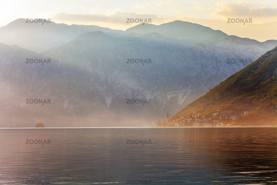 Sunset on the sea with theа foggy mountains