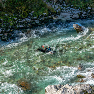 kayaker paddling on the clear turquoise waters of the Soca River in the mountains of northern Slovenia