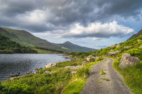 Winding country road leading trough Black Valley, MacGillycuddys Reeks mountains