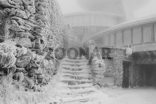 Frost-covered, frozen abandoned building. Black and white.