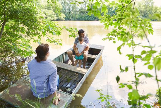 Familie mit Kind macht Ausflug in einem Boot am See