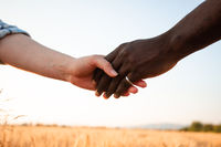 Multiracial relationship and friendsip concept. Two hands holding together.