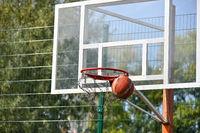Shooting orange basketball ball into the basket