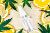 Cannabis Terpene bottle with leafs lemon orange citrus on wooden backdrop