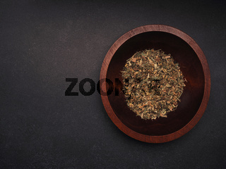 Organic herbal tea in a wooden bowl on a dark stone table, view from above