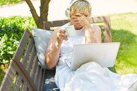 Frau sitzt mit der Hand vor dem Gesicht am Laptop