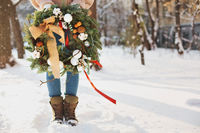 Crop woman with Christmas wreath on snow