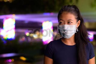 Asian woman thinking and wearing face mask to protect from covid 19 outdoors at night