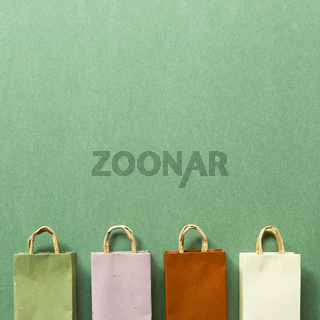 Paper shopping bags on green background. top view, copy space