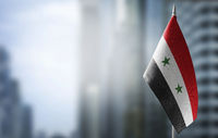 A small flag of Syria on the background of a blurred background