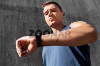 young man with fitness tracker on city street