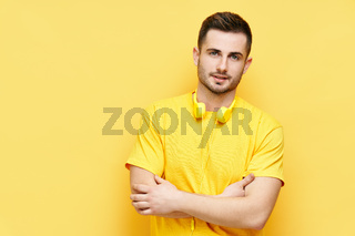 Trendy handsome man with crossed arms and headphones looking to camera