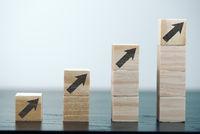 upwards pointing arrow symbols on stacks of wooden blocks