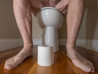 Senior adult man sitting on toilet with roll of paper in bathroom