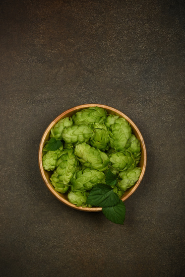 Wooden bowl of fresh green hops on table
