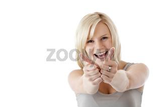 Junge blonde Frau hält lächelnd beide Daumen nach oben