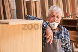 Senior Handwerker als Meister mit Mundschutz