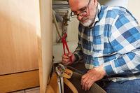 Installateur sucht Werkzeug  zur Reparatur der Spüle