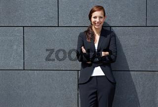 Geschäftsfrau lehnt an Wand