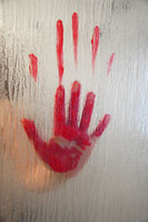 bloody hand behind frosted glass window or shower screen
