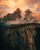 hiker on top of mountain in dolomites at cadini di misurina during sunset in summer