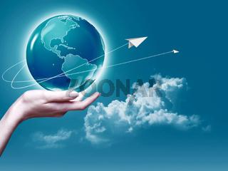 Female arm holding Earth  globe against blue skies, environmental backgrounds