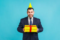 Smiling businessman wearing official style suit and party cone holding gift and looking at camera with toothy smile, gifts and bonuses, celebration.