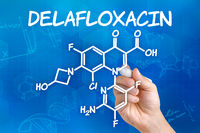 Hand with pen drawing the chemical formula of Delafloxacin