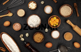 Baking ingredients pattern on black background, top view