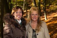 Zwei hübsche und fröhliche Frauen mit Herbstwald im Hintergrund