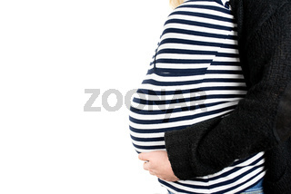 close-up side view of baby bump of nine months pregnant woman wearing striped top and wool cardigan