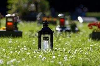 Gräber mit Grablaternen auf einer blühenden Frühlingswiese